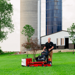 Hired lawn care professionals in Overland Park mowing a lawn